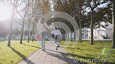 Uma mulher e uma garotinha de uniforme na escola correndo no parque, Steadicam, vista de trás video estoque
