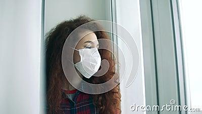 Uma mulher maravilhosa numa máscara facial está olhando para dentro da janela vídeos de arquivo