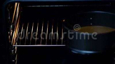 Uma mulher põe uma massa em um formulário em um forno - close up video estoque
