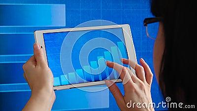 Uma mulher segura um tablet nas mãos contra o fundo de um quadro em movimento, analisando o crescimento do lucro, o plano de negó video estoque