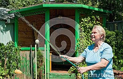 Uma mulher sênior com água no jardim