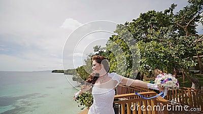 Uma noiva de brilho aprecia a felicidade da altura do balcão que negligencia o oceano e os recifes Voo do amor exotic video estoque