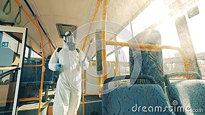 Uma pessoa de fato perigoso está descontaminando quimicamente o ônibus Pessoas com vestuário protetor pulverizam produtos químico video estoque