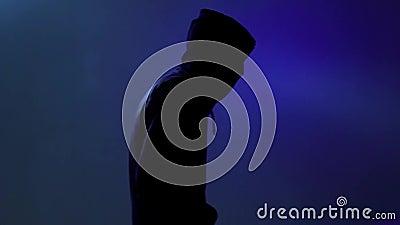 Uma pessoa impessoal hunched sobre e voltas à câmera O homem abstrato na roupa preta com uma capa passa sobre um CCB luminoso azu vídeos de arquivo