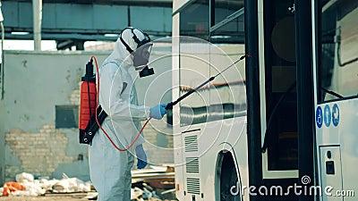 Uma pessoa num terno perigoso está pulverizando produtos químicos no ônibus filme