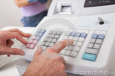 Uma quantidade entrando da pessoa das vendas no registo de dinheiro