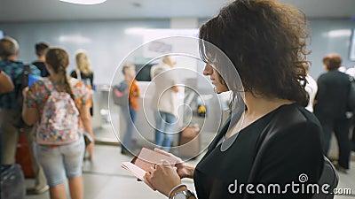 Uma senhora bonita está verificando seu passaporte antes da viagem vídeos de arquivo