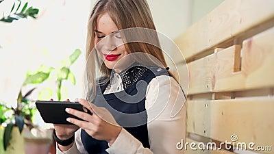 Uma senhora doce olha fotos em redes sociais em seu telefone celular video estoque