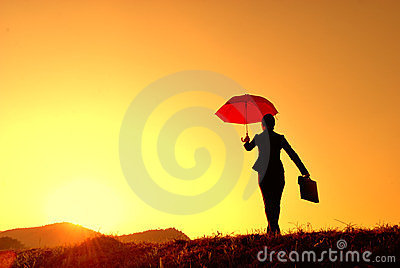 Umbrella business woman and sunset silhouette