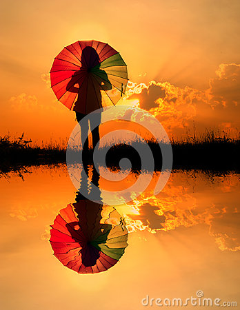 Umbrella woman and sunset silhouette,Water reflect