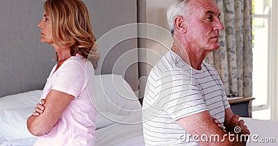 Umgekippte ältere Paare, die zurück zu Rückseite auf Bett sitzen stock footage