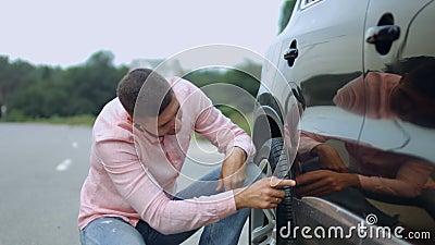 Umgekippter Fahrer, der Kratzer und Einbuchtungen auf Auto betrachtet stock footage