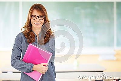 Uśmiechnięta nauczyciel pozycja w sala lekcyjnej