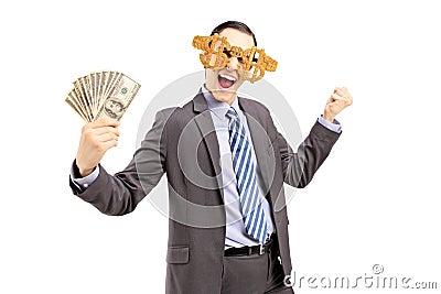 Uśmiechnięty mężczyzna jest ubranym dolarowych szkła i trzyma dolary w kostiumu