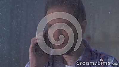 Umkippenmann, der am Telefon, schlechte Nachrichten am regnerischen Tag empfangend, relativer Tod spricht stock video