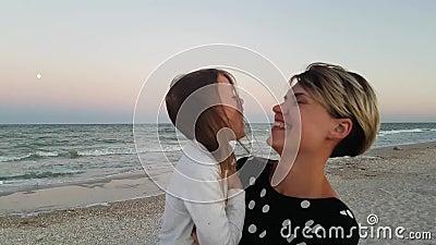 Umkreisen des Kindes Glückliche Familie im Hintergrund des Meeres Mutter mit Tochter hat Spaß am Strand stock footage