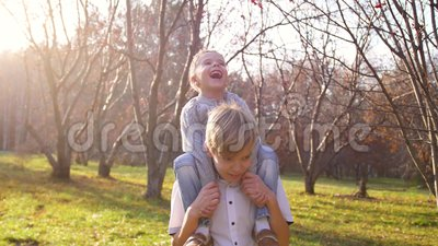 Un'adolescente gioca con un bambino, tenendolo tra le braccia I raggi solari penetrano i bambini La risata e la gioia archivi video