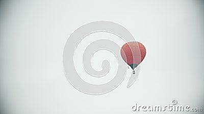 Un aerostato arancio che vola su un fondo del cielo bianco video d archivio