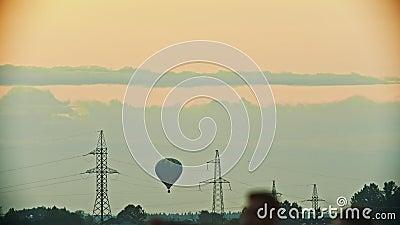 Un aerostato blu-e-giallo che sorvola il campo - torri di comunicazione, torri di antenna - sera video d archivio