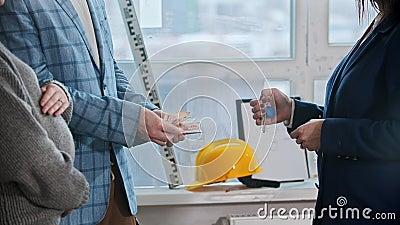 Un agente inmobiliario sostiene llaves y un hombre cuenta el dinero para el alquiler del apartamento almacen de metraje de vídeo