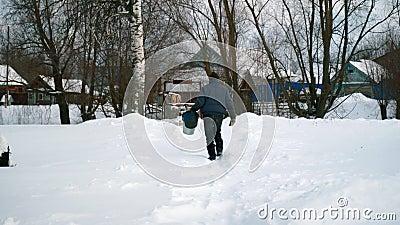 Un anciano con baldes va al pozo por agua Un anciano en invierno en la aldea va por agua almacen de metraje de vídeo