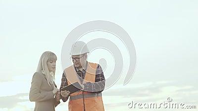 Un appaltatore in una maglia ed in un casco riflettenti fa un affare con una signora di affari sui precedenti dei mulini a vento video d archivio