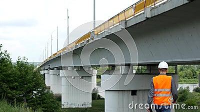 Un architecte d'homme examine l'état du pont au-dessus de la rivière et enregistre les données, pont clips vidéos