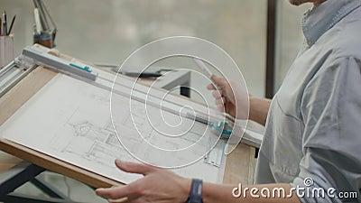 Un arquitecto sentado en una mesa dibuja un plano del edificio y se dedica al desarrollo del diseño, sentado en el almacen de metraje de vídeo