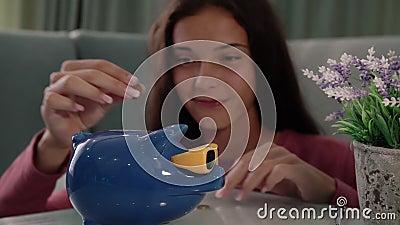 Un'attrattiva brunetta prende le monete metalliche in una banca blu di porcellini stock footage