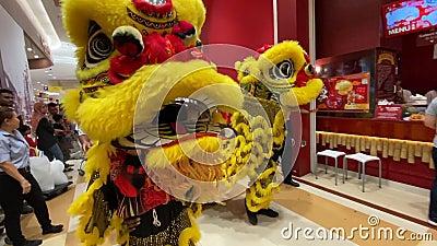 Un baile del león en un centro comercial para celebrar el próximo Año Nuevo Chino almacen de metraje de vídeo