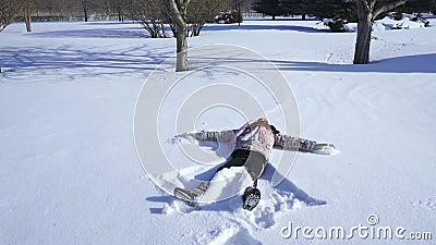 Un bambino fa un angelo della neve video d archivio