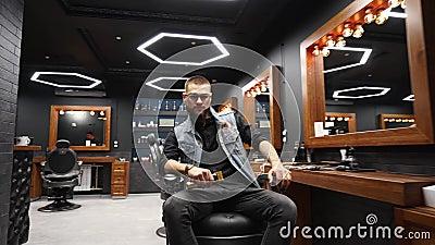 Un barbero profesional que gira sentado en una silla vintage y que mira la cámara sujetando un caprichoso en la mano en la barber metrajes