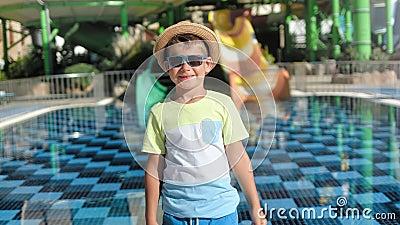 Un bebé viajero de moda con gafas de sol y gorro apuntando al tobogán de agua del patio de recreo cerca de la piscina almacen de metraje de vídeo