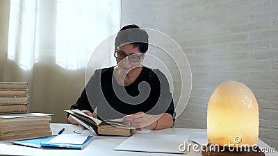 Un bibliothécaire vérifie les livres après les lecteurs Une femme feuilletant des livres dans la bibliothèque sur fond de lampe s clips vidéos