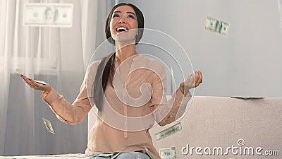 Un bon nombre d'argent liquide tombant sur la fille étonnée heureuse, durées du prêt favorables de banque, argent banque de vidéos