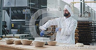 Un boulanger charismatique à la barbe dans une grande boulangerie en train de danser en travaillant à sa table prendre la pâte et banque de vidéos