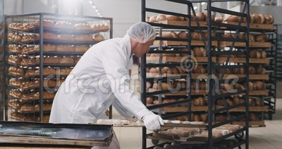 Un boulanger professionnel vieil homme bon à l'air de prendre le grand plateau plein de pain cru et de charger sur les étagères banque de vidéos