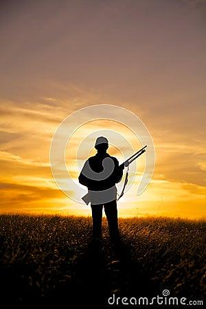 Cazador del rifle en puesta del sol