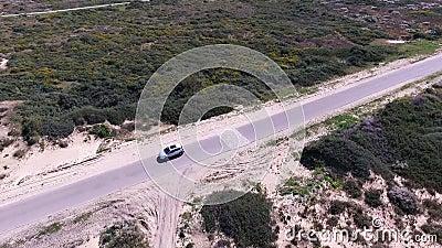 Un coche blanco está conduciendo a lo largo del camino en el desierto metrajes