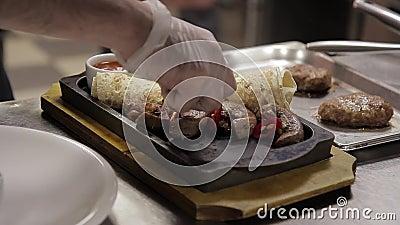 Un cocinero adorna un plato con la carne y el pan Pita en una bandeja del metal almacen de metraje de vídeo