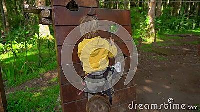 Un colpo lento di due ragazzini in un cavo di sicurezza in un parco di avventura della foresta Centro all'aperto di divertimento  stock footage