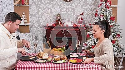Un couple caucasien dégustant un dîner de Noël et des verres clinquants avec du champagne banque de vidéos