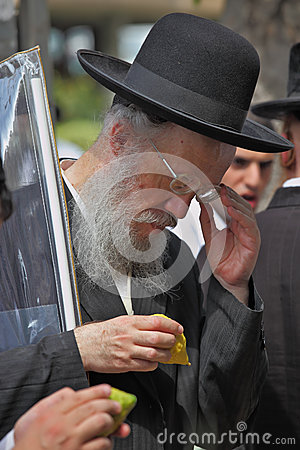 Un ebreo ortodosso anziano in cappello nero seleziona l agrume Fotografia Editoriale