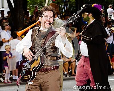 Un ejecutante del musical juega para la muchedumbre en el desfile Imagen de archivo editorial