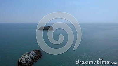 Un en avant aérien indique la longueur d'un littoral rocheux vers la roche de deux îles avec de l'eau turquoise sous un ciel bleu banque de vidéos