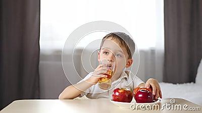Un enfant heureux boit du jus d'Apple et mange une pomme, assis à une table dans la pièce Alimentation des enfants, écologie banque de vidéos