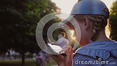 Un enfant joue sur un smarphone, il est assis dans un parc sur un banc banque de vidéos