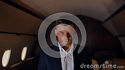 Un entrepreneur qui regarde la caméra dans un avion d'affaires banque de vidéos
