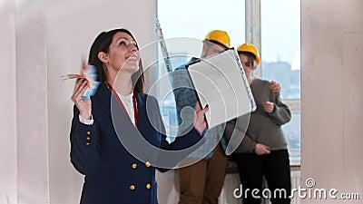 Un feliz agente inmobiliario saludando con dinero en efectivo - pareja de jóvenes casados mirando alrededor del fondo metrajes