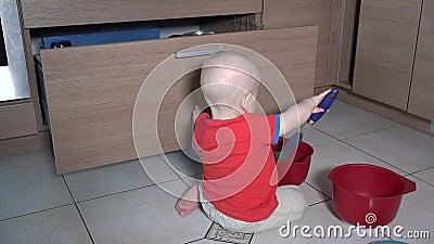 Un gamin en train de faire du gâchis en cuisine Jouer avec des bols et des ustensiles banque de vidéos